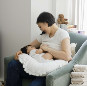 Mother breast feeding baby girl